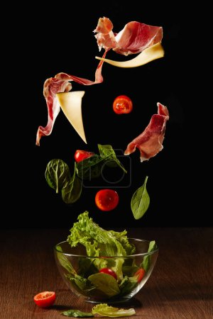 Ingredients for salad of vegetables and jamon falling in bowl above wooden table