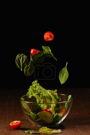 Photo for Tomatoes and salad leaves falling in bowl above wooden table surface - Royalty Free Image