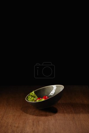 Ripe tomatoes and salad leaves in bowl on wooden table