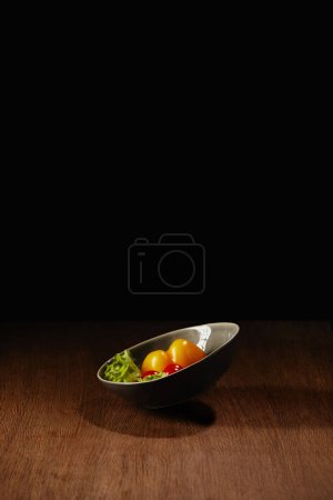 Bowl with tomatoes and salad leaves on wooden table