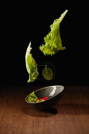 Photo for Fresh organic salad flying above wooden table surface - Royalty Free Image