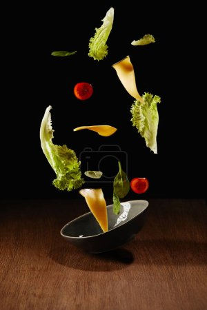 Fresh salad with cheese slices and bowl flying above wooden table surface