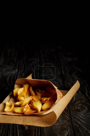 Golden french fries in craft paper on wooden table