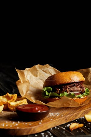 Photo for Hamburger and french fries with salt and sauce on wooden board - Royalty Free Image