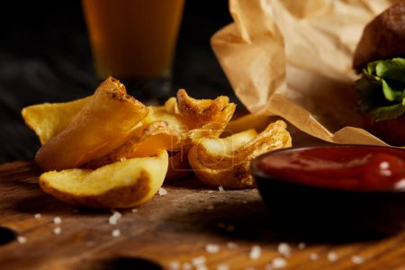 Photo for Hamburger and french fries served with sauce on wooden board - Royalty Free Image