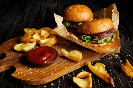 Photo for Tempting fast food diner with burgers and potatoes with sauce on cutting board - Royalty Free Image
