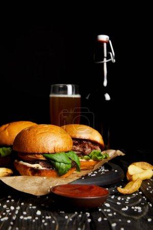 Photo pour Jeu de hamburgers de la malbouffe sur table avec de la bière en bouteille et verre - image libre de droit