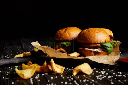 Photo for Set of junk food hamburgers and fried potatoes with scattered salt on wooden table - Royalty Free Image