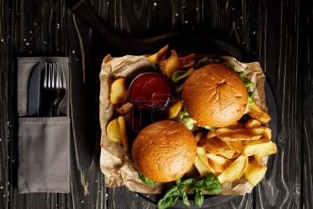 Photo for Hamburgers and french fries served on board by cutlery set - Royalty Free Image