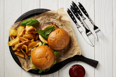 Top view of tempting hamburgers and french fries with sauce and cutlery on white table