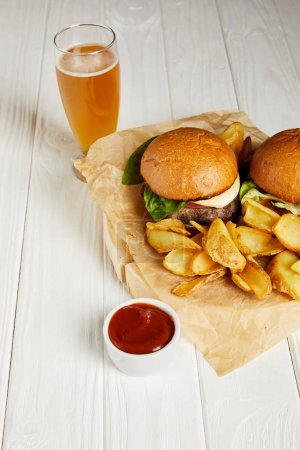 Photo for Set of junk food burgers and fries served with beer on white table - Royalty Free Image