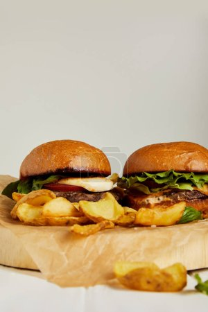 Photo for Hot hamburgers and french fries served on craft paper - Royalty Free Image