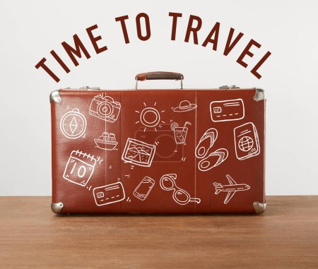 Vintage brown leather suitcase with icons and lettering - Time to travel