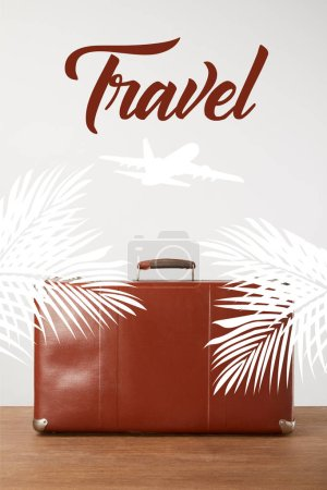 Vintage brown leather suitcase with palm leaves, airplane and travel lettering