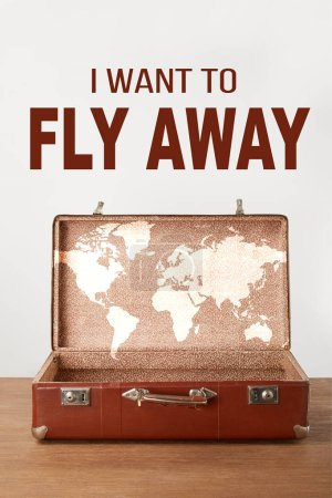 """Open vintage suitcase with map and """"I want to fly away"""" lettering"""