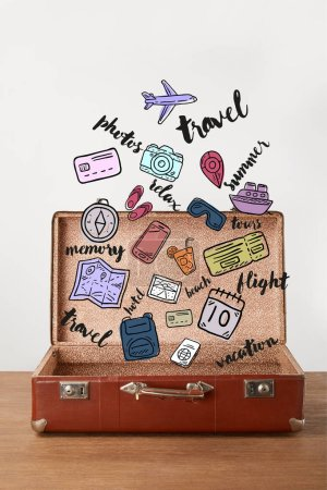 Photo for Open vintage suitcase with travel icons - Royalty Free Image