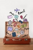 Open vintage suitcase with travel icons