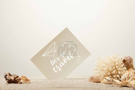 "close up view of coral, seashells and blank card on sand on grey background with ""lets go travel"" lettering"