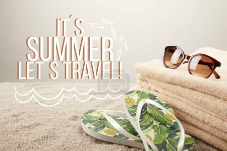 "close up view of stack of towels, sunglasses and summer flip flops on sand on grey backdrop with ""it is summer lets travel"" inspection"