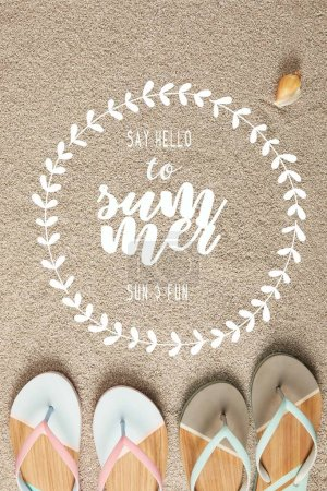 """flat lay with summer flip flops and seashell on sand with """"say hello to summer"""" lettering in floral frame"""