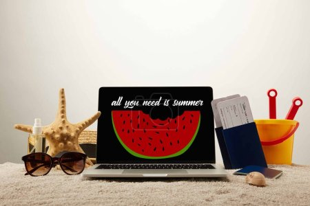 "close up view of laptop  with ""all you need is summer"" lettering and watermelon illustration, sea star, sunglasses, passports with tickets and toy bucket on sand on grey background"