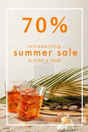 Photo pour Vue rapprochée de chapeau de paille, cocktails, coquillages, lunettes de soleil et feuille de palmier sur sable sur fond gris avec rabais de vente d'été - image libre de droit