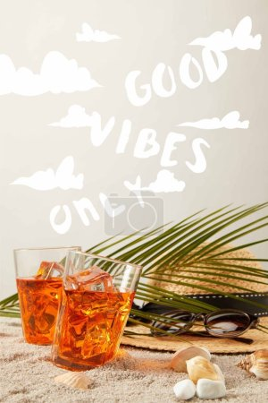 "Photo for Close up view of straw hat, cocktails, seashells, sunglasses and palm leaf on sand on grey backdrop with ""good vibes only"" sign - Royalty Free Image"
