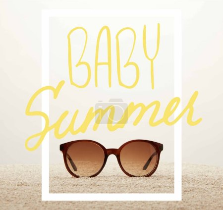 """close up view of sunglasses on sand on grey background with """"baby summer"""" symbol"""