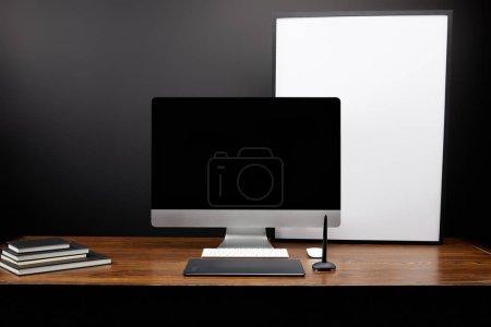 Photo pour Bouchent la vue du milieu de travail concepteur graphique avec la tablette graphique, écran d'ordinateur vierge, carnets et tableau blanc vide sur une table en bois - image libre de droit