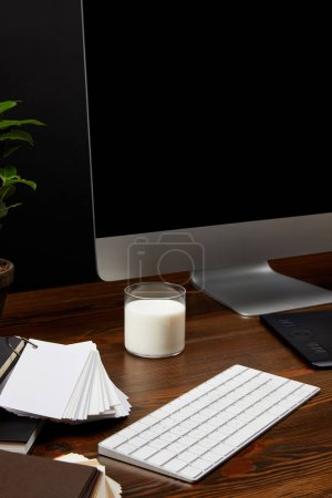 close up view of designer workplace with glass of milk, computer screen and keyboard on wooden tabletop