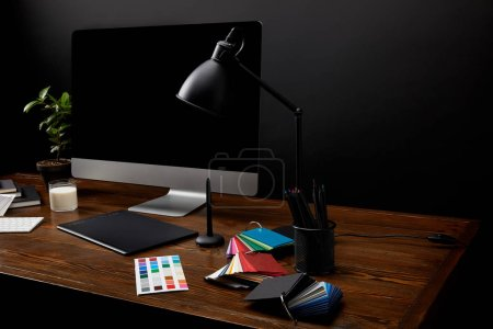 Photo for Close up view of graphic designer workplace with colorful pallet, graphic tablet, computer screen and lamp on wooden surface - Royalty Free Image