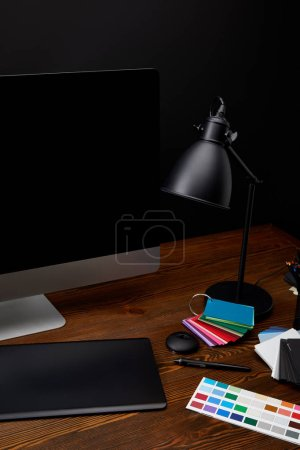 close up view of graphic designer workplace with colorful pallet, blank computer screen, lamp and graphic tablet on wooden surface