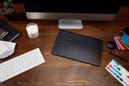 Nahaufnahme des Grafikdesignerarbeitsplatzes mit Palette, Milchglas, Grafik-Tablet und Computerbildschirm auf hölzerner Tischplatte
