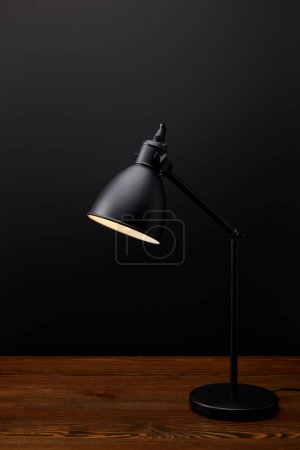 close up view of black lamp on wooden tabletop on black background