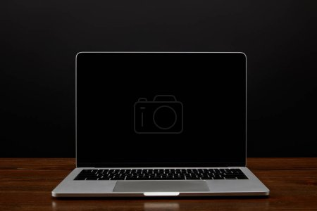 close up view of laptop with blank screen on wooden tabletop on black wall backdrop