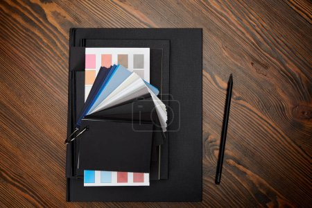flat lay with black notebooks, colors pallet and pencil on wooden tabletop