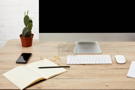 close up view of designer workspace with smartphone, notebook, computer screen and keyboard on wooden surface