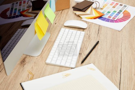 close up view of designer workplace with computer screen with colorful stickers, notebooks and pallet on wooden tabletop