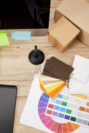 Photo for Top view of graphic designer workplace with arranged computer screen, colorful stickers, graphic tablet and pallet on wooden surface - Royalty Free Image