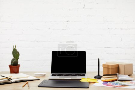 Photo for Close up view of laptop, graphic tablet, notebooks and pallet on wooden surface at graphic designer workplace - Royalty Free Image