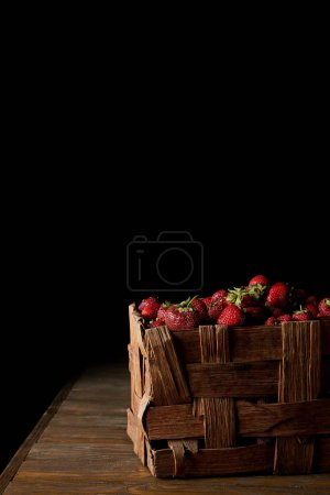 freshly harvested ripe strawberries in rustic box on black