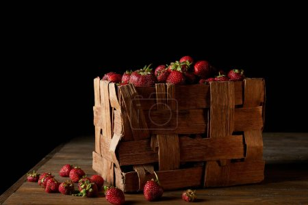 ripe strawberries in rustic box on wooden surface and on black