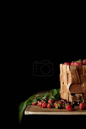 ripe cherries and strawberries on wooden tabletop and on black