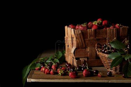 Photo pour Cerises et fraises fraîchement récoltées sur table en bois et sur fond noir - image libre de droit