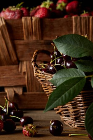 close-up shot of cherries and strawberries in basket and box