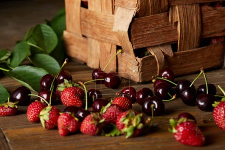 ripe cherries and strawberries on wooden surface with leaves and rustic box