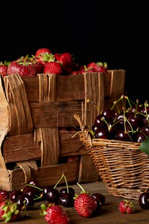 fresh cherries and strawberries in basket and box isolated on black