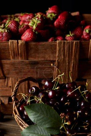 fresh ripe cherries and strawberries in basket and box