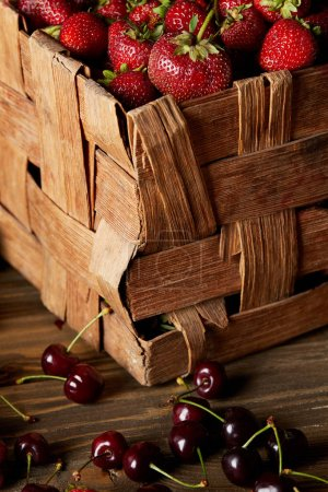 close-up shot of cherries on wooden tabletop with strawberries in rustic basket