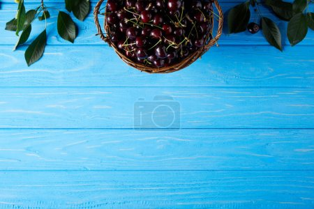 top view of fresh cherries in basket on blue wooden surface